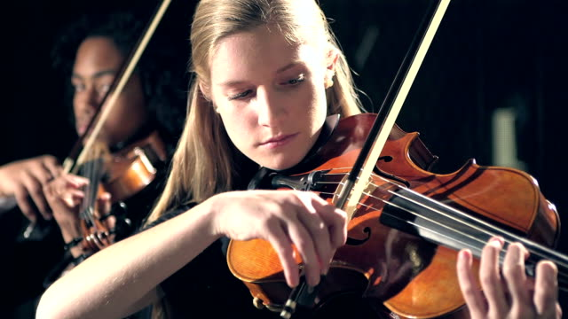 vídeos de stock e filmes b-roll de teenagers playing violin in concert - instrumental
