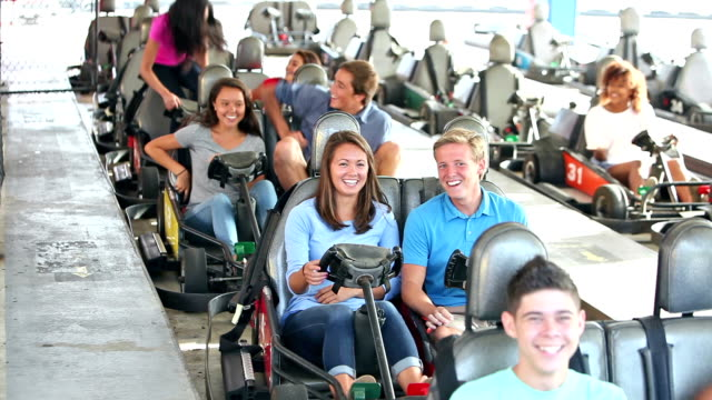 Teenagers riding go-carts at amusement park, getting in A multi-ethnic group of nine teenagers, 16 to 18 years old, riding go-carts at an amusement park. They are at the start of the ride, running up and climbing into the cars. go cart stock videos & royalty-free footage