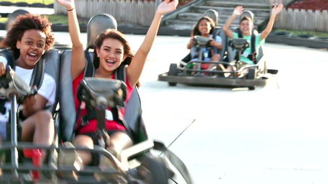 Teenagers riding go-carts at amusement park A multi-ethnic group of nine teenagers, 16 to 18 years old, riding go-carts at an amusement park on a curvy race track. go cart stock videos & royalty-free footage