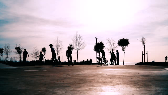 Teenagers skateboarding,riding kick scooters and cycling on urban skate park Silhouettes of teenagers on urban skate park low lighting stock videos & royalty-free footage