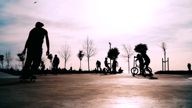 Teenagers skateboarding,riding kick scooters and cycling on urban skate park