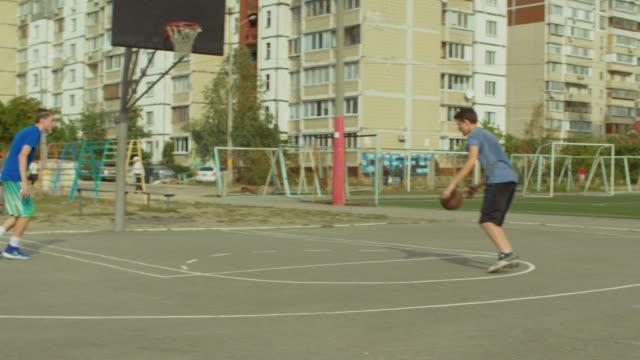 vídeos de stock e filmes b-roll de teenagers training basketball skills on outdoor court - europe points
