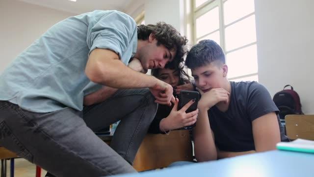 подростки, использующие мобильный телефон и улыбающиеся в классе - поколение z стоковые видео и кадры b-roll