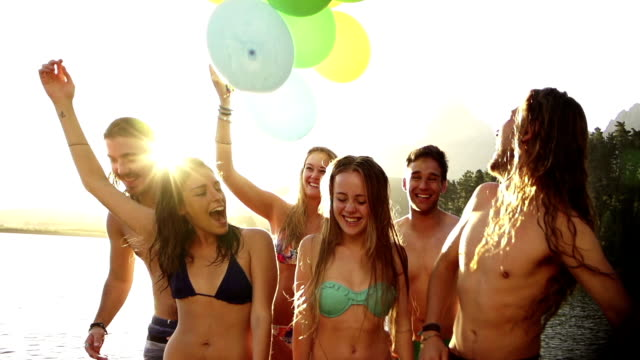 Teenagers with balloons on a jetty video