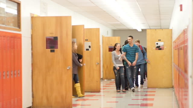 Teens exit their classrooms -Uberstock- HD 1080p-  As class ends, all the students leave their classrooms and begin walking and talking in halls.  Wide shot.  locker stock videos & royalty-free footage