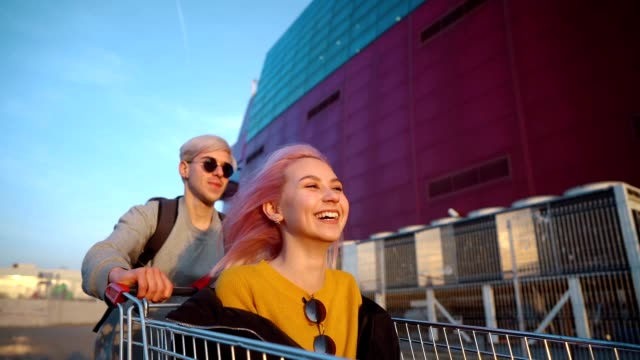 teens in exciting ride with shopping cart - attività del fine settimana video stock e b–roll