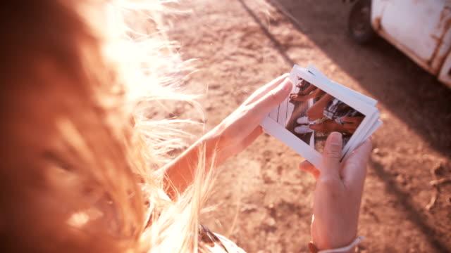 stockvideo's en b-roll-footage met teens looking at instant photos outdoors on summer afternoon - polaroid