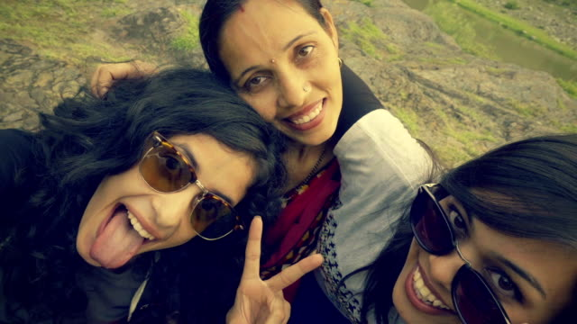 Teens taking fun selfie in fresh air. Outdoor video of teenage girls taking selfie together with friends and family in their vacation in hills. indian family stock videos & royalty-free footage