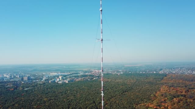 telecommunication antenna for television and radio broadcasting is located outside the city near the forest.