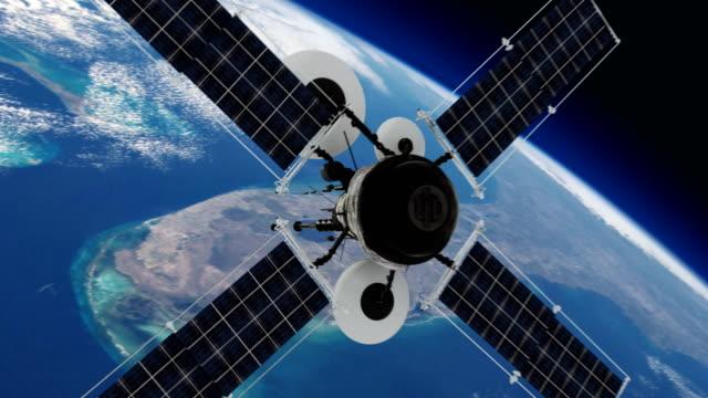 telecommunication satellite orbiting earth. - вид со спутника стоковые видео и кадры b-roll