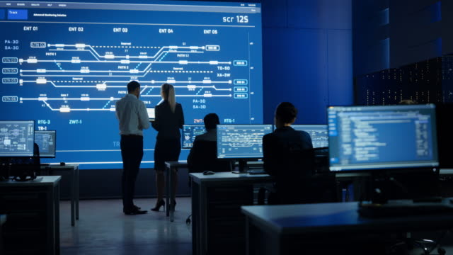 telecommunications company system control and monitoring room with diverse multicultural team of professionals working on computers. big screen display showing infrastructure infographics. back view - centrale elettrica video stock e b–roll