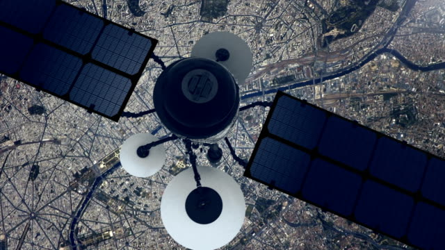 Telecomunication satellite sending signal to Earth. Flying over large city