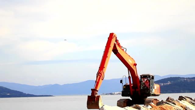 vídeos de stock, filmes e b-roll de telescopic excavator em quebra-mar - pesado peso