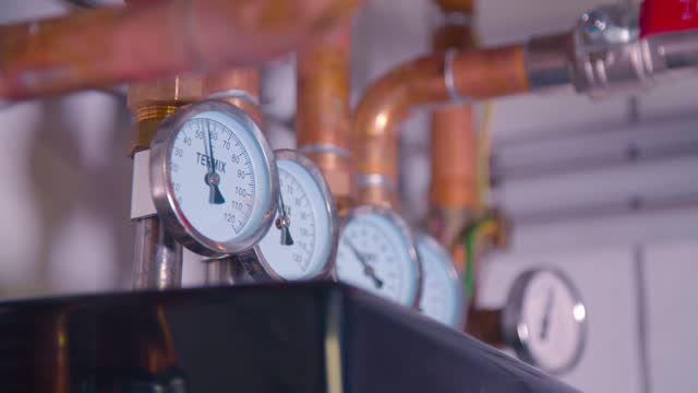 temperature meters and copper pipes in boiler room