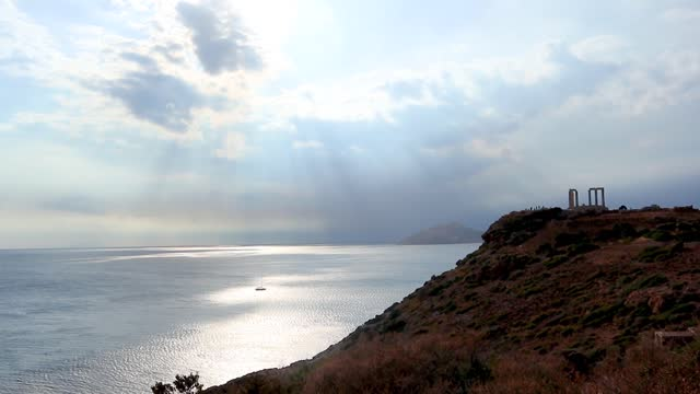 Temple of Poseidon with blue Greece Aegean sea High rocky seashore cliff view on Temple of Poseidon with blue Greece Aegean sea in sunset light. Summer travel marine landscape sounion stock videos & royalty-free footage