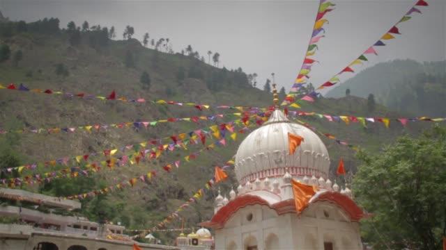 tempel befindet sich in einem niedrigeren himalaya ist mit bunten wimpeln oder gebetsfahnen verziert. - kieferngewächse stock-videos und b-roll-filmmaterial