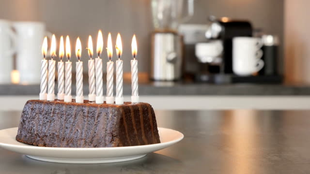 vídeos de stock e filmes b-roll de ten candles on a birthday cake burning down to be blown out in a modern kitchen - sideboard