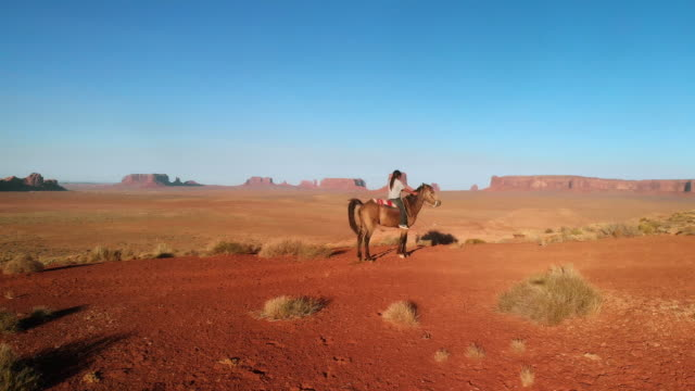 Ten Year Old Native American Navajo Boy with Very Long Hair Bareback Horseback Riding in the Northern Arizona Desert Near Monument Valley Tribal Park at Dusk in the Summer