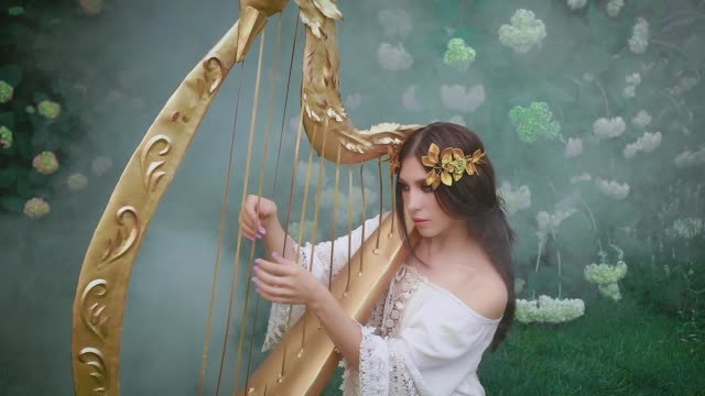 Tender girl cute angelic face plays an elven song melody on harp. Greek goddess