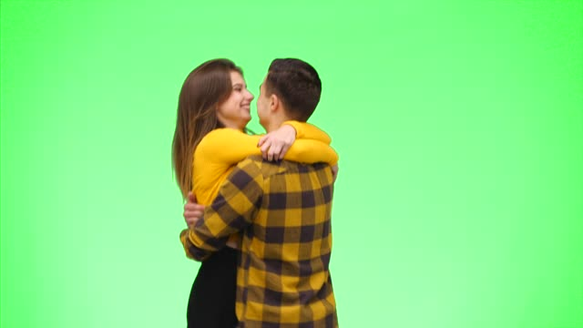 Tender loving couple is coming into a focus and smiling sincerely on a green background. Crop. Copy space. 4K.