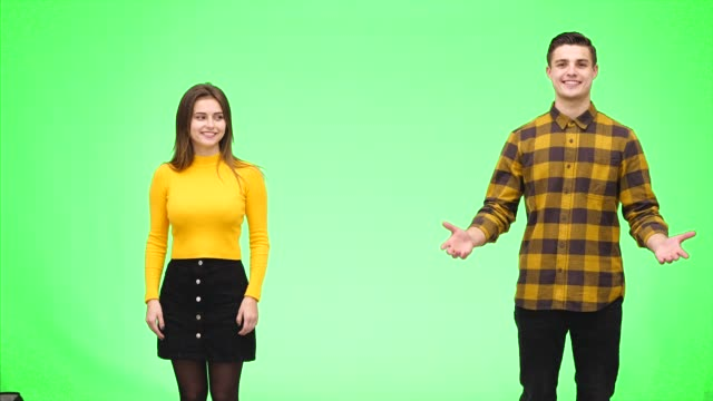 Tender loving couple is smiling sincerely and showing something with open hands, on a green background. Close up. Copy space. 4K.