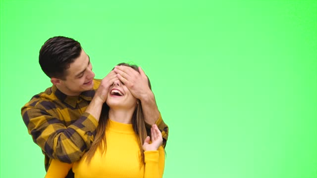 Tender loving couple is smiling sincerely and snuggling on a green background. Close up. Copy space. 4K.
