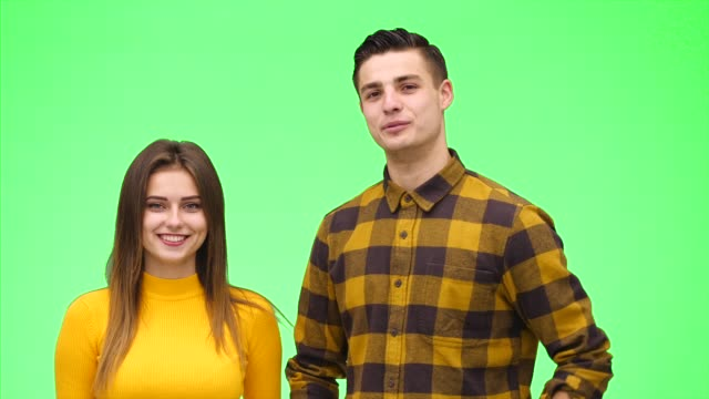 Tender loving couple is smiling sincerely on a green background. Close up. Copy space. 4K.