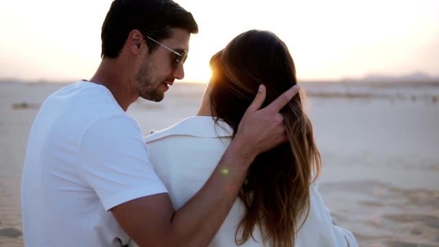 Zärtliche Momente zwischen einem liebevollen jungen Paar, das allein in der trockenen Wüste auf dem Sand sitzt. Mann streichelt seine Frau. Tragen sie beide weißen T-Shirts. Sinnlicher Moment des liebevollen Paares – Video