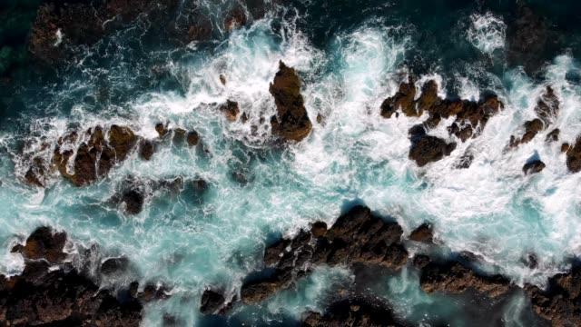 特內里費,西班牙,金絲雀。落基海岸在輕風暴中,綠松石波浪衝擊海岸。空中自上而下拍攝,uhd - 懸崖 個影片檔及 b 捲影像