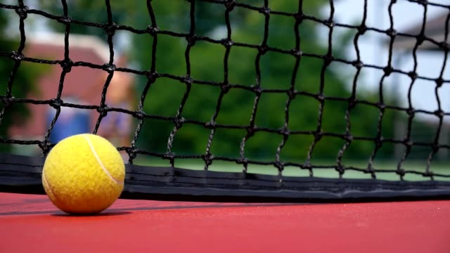 Tennis Ball on the Court Close up with the Net Beyond video