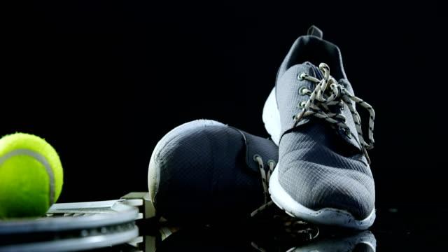 Tennis balls, racket and sports shoe in studio 4k video