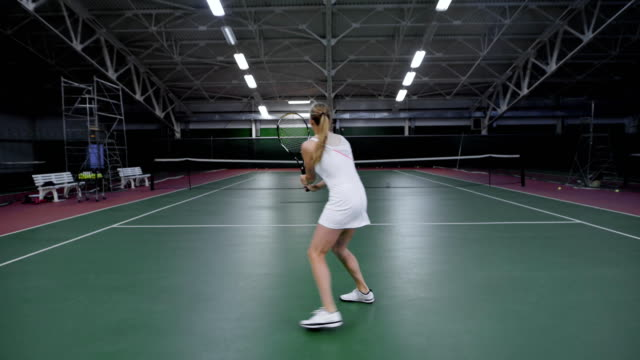 Tennis game. Beautiful woman player playing with man in tennis video
