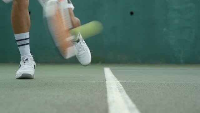 Ein Tennisspieler, der einen Schuss von der Grundlinie aus spielt. – Video