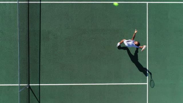 Ein Tennisspieler, der rückwärts läuft, schlägt einen Schuss und feiert. – Video