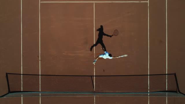 Ein Tennisspieler läuft über einen Lehmplatz, gibt den Schuss zurück und feiert. – Video