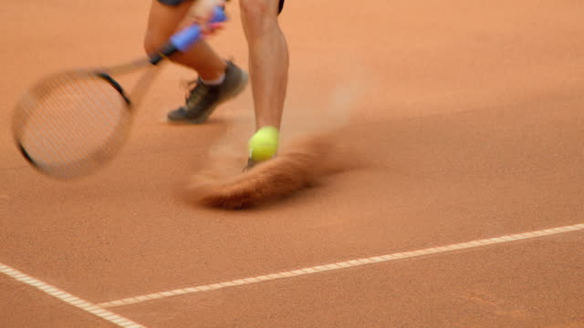 A Tennis player runs across a clay tennis court to play the shot. A Tennis player sliding across court to play a shot in slow motion. teknik stock videos & royalty-free footage
