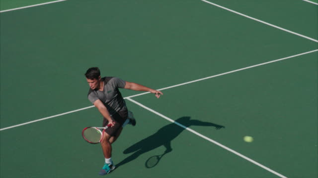 Ein Tennisspieler läuft über Hof, gewinnende Schuss zu machen. – Video