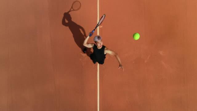 Ein Tennisspieler serviert und feiert und