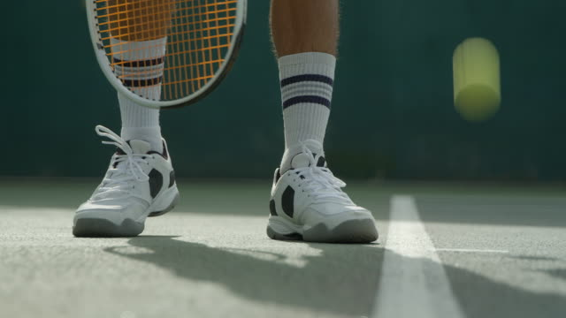 A Tennis Player Serves as he jumps out of the shot. A Tennis Player bounces the ball ready to serve and then serves leaving the shot. teknik stock videos & royalty-free footage