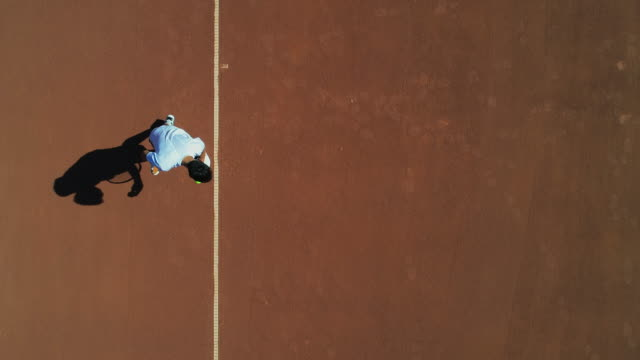 Ein Tennisspieler dient von oben auf einem Lehrplatz. – Video