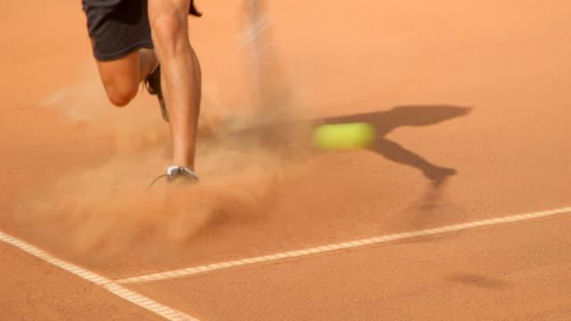 Ein Tennisspieler rutscht über einen Sandplatz, um einen Schuss zu spielen. – Video