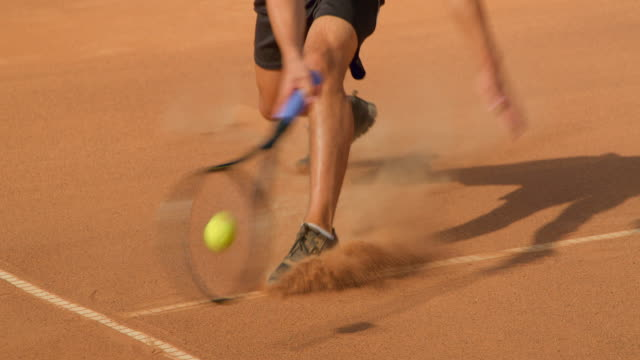 A Tennis player slides into the shot to play a close to the line call. A Tennis player sliding across a clay tennis court plays a shot that could be in  or out. match sport stock videos & royalty-free footage