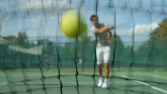 Ein Tennisspieler schlägt einen Ball ins Netz, wirft seinen Schläger zu Boden und tritt in die Luft. – Video