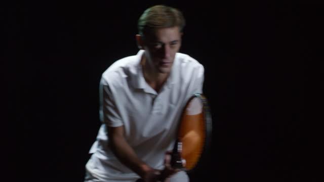 黒の背景に待ってテニス選手サーブします。 - テニス点の映像素材/bロール