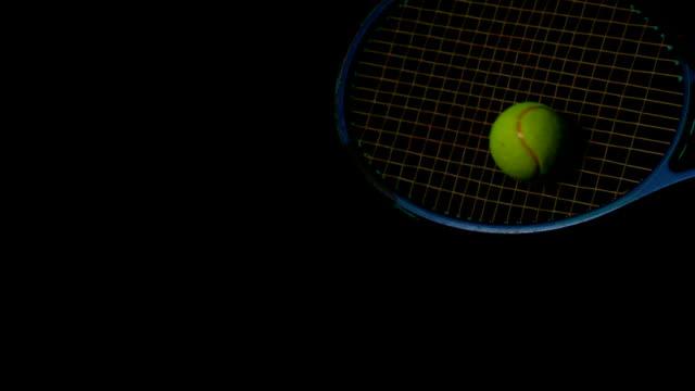 Tennis racket hitting a ball on black background video