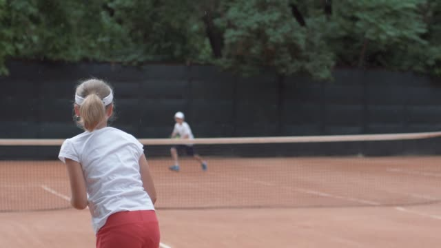 tennis, sports player teenager girl with rivals hitting racket on ball pass through net to each other at court during tournament - campionato video stock e b–roll