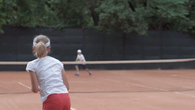 stockvideo's en b-roll-footage met tennis, sport speler tiener meisje met rivalen raken racket op bal passeren via net aan elkaar bij de rechtbank tijdens het toernooi - kampioenschap