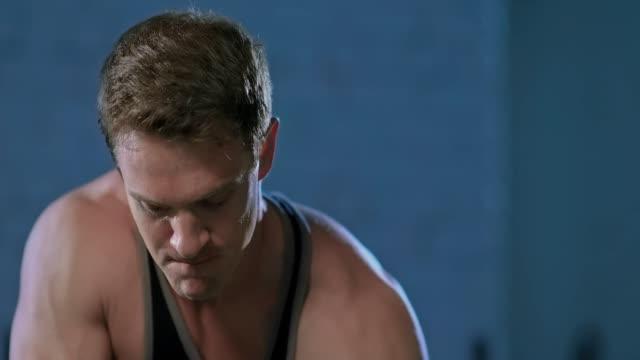 緊張した、筋肉の胴体に残忍な男の深刻な外観。男性アスリートは彼の手の筋肉を振る。縦向きのビュー。 - 人の筋肉点の映像素材/bロール