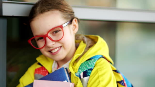 vídeos de stock e filmes b-roll de ten-year schoolgirl happily smiling at the camera. the girl in red glasses and a yellow jacket with textbooks in their hands - setembro