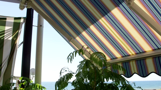 Terrace with retractable striped awnings with sea view video